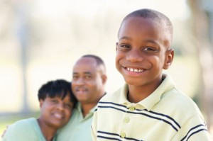 Handsome African American Boy with Proud Parents Standing By in the Park.